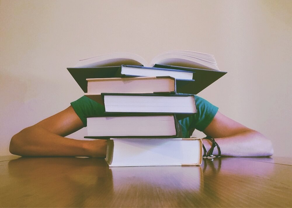 girl hiding behind books
