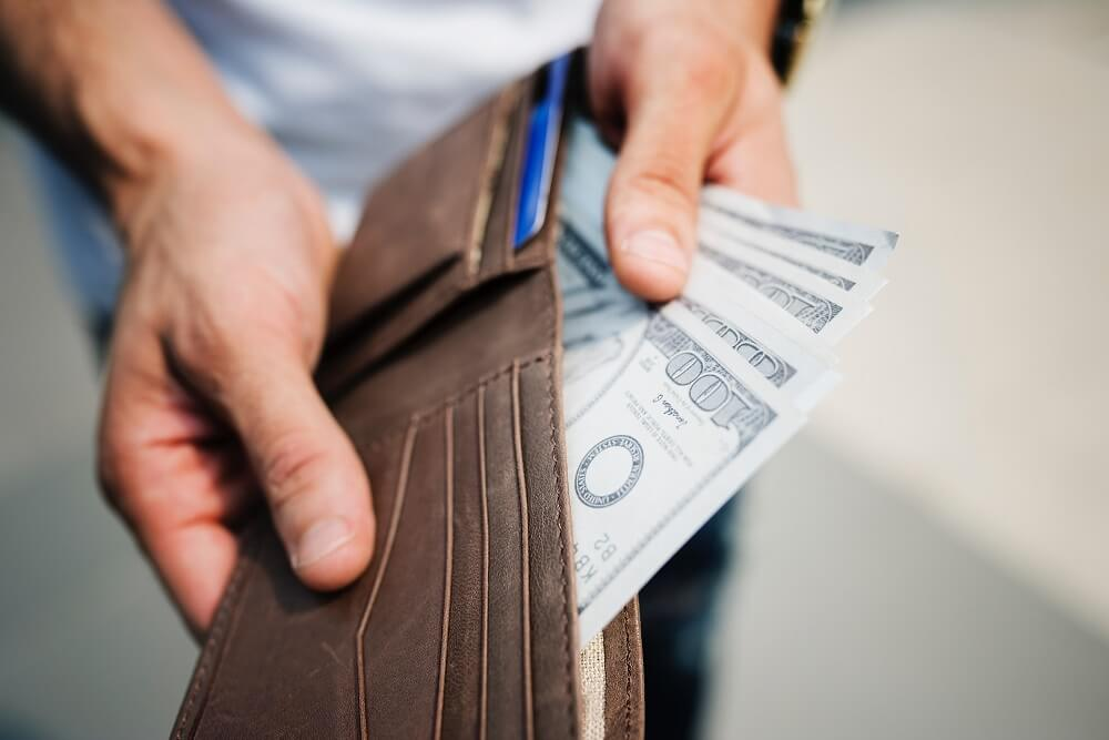 man holding money full of wallet
