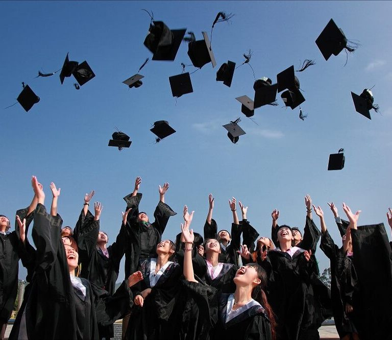 students throwing hats at graduation ceremony