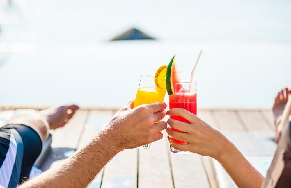 couple with cocktails on beach