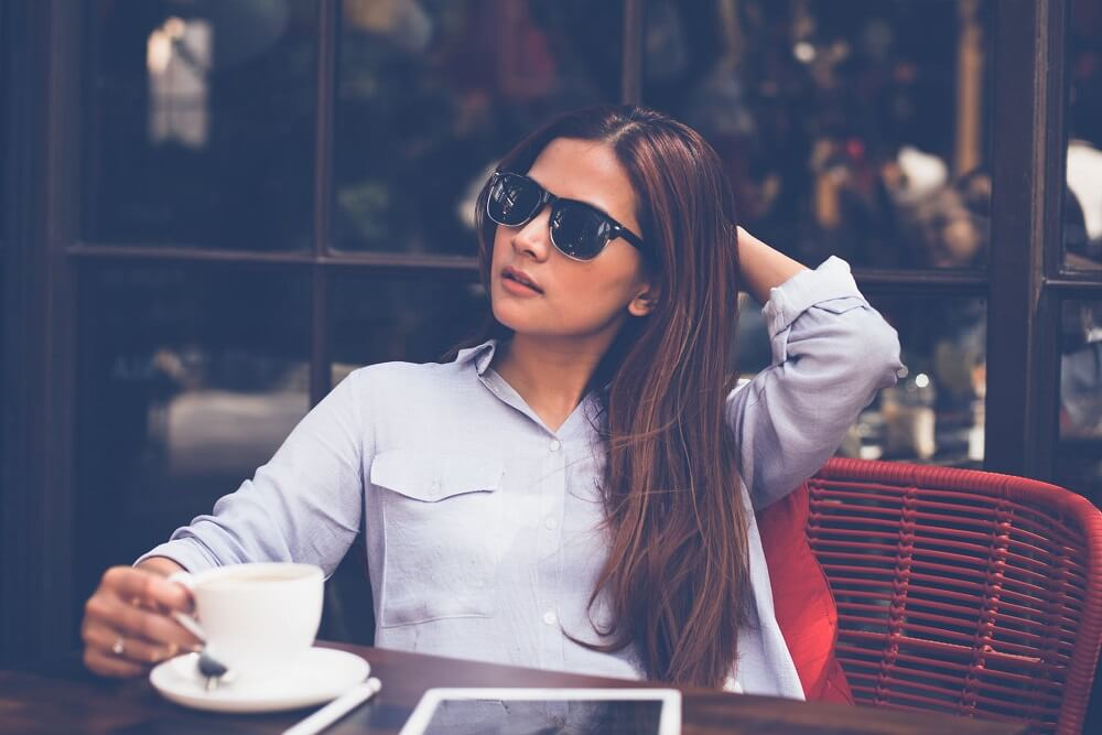 woman sitting at table drinking coffee