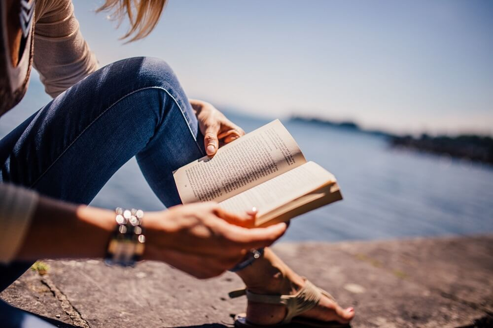 women reading a book outside