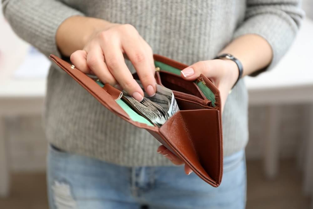 woman showing wallet with money in it
