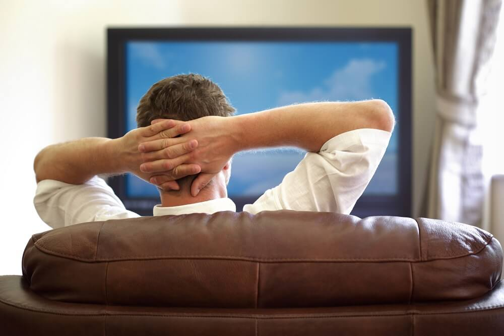 man relaxing couch watching tv