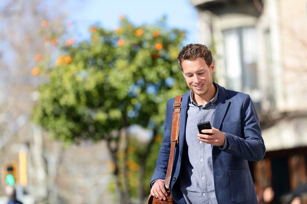 man walking while texting on cellphone