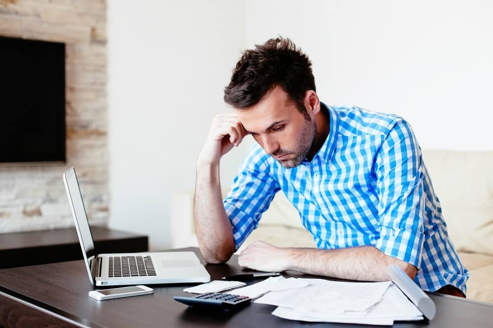 man stressed out looking out bills
