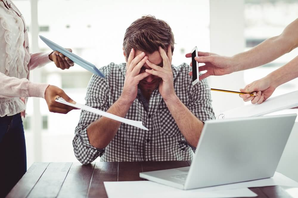 man overwhelmed at work