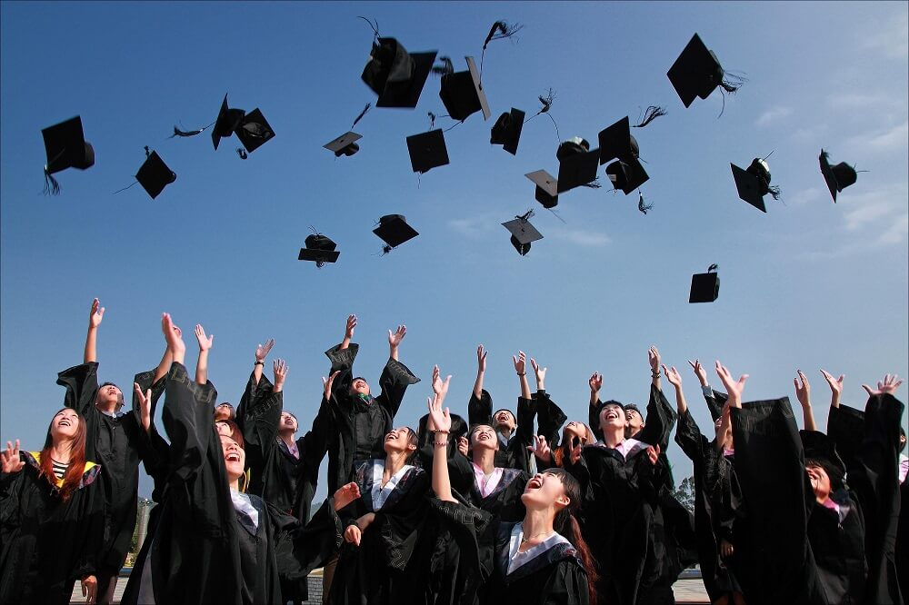 college students throwing hats at graduation