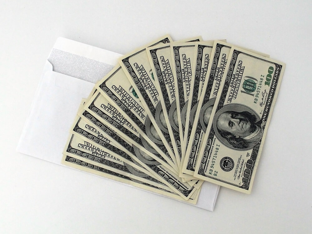 dollar bills lying on envelope