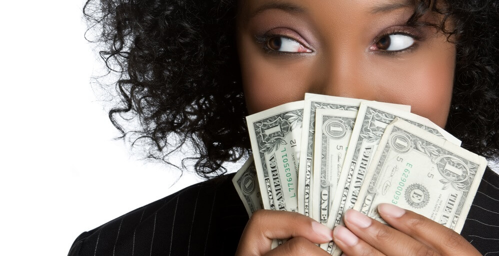 woman holding cash - how to pay off debt fast on low income article