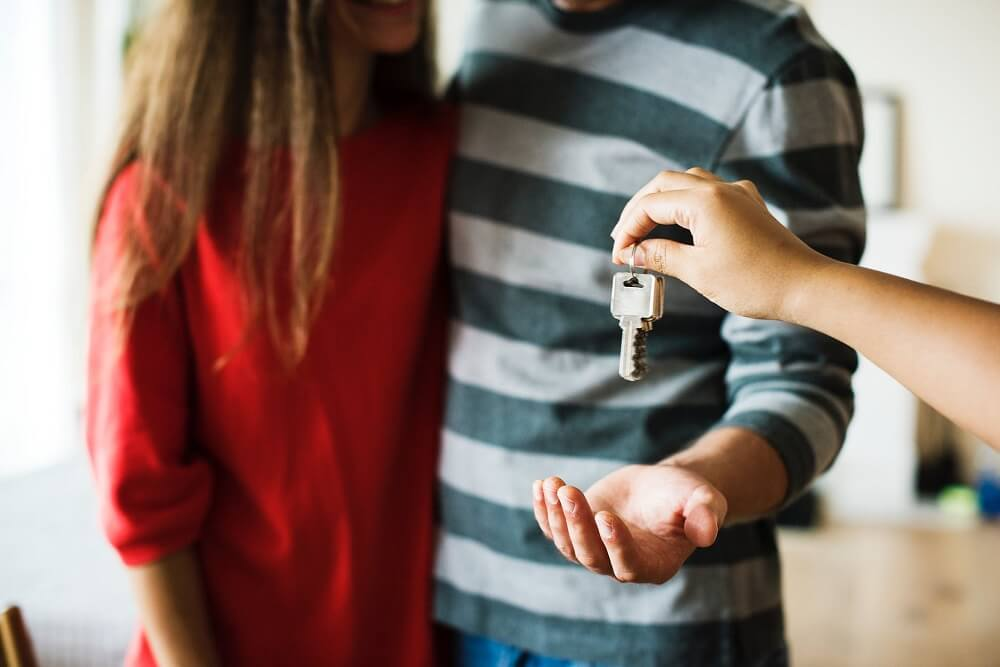 man and woman getting keys to new house