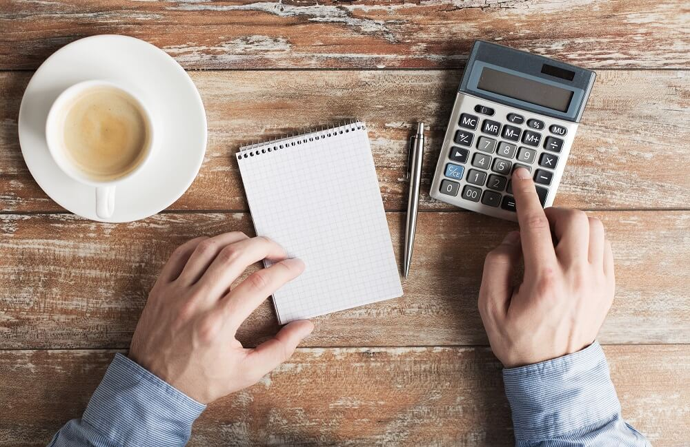 man with calculator and notepad doing bills