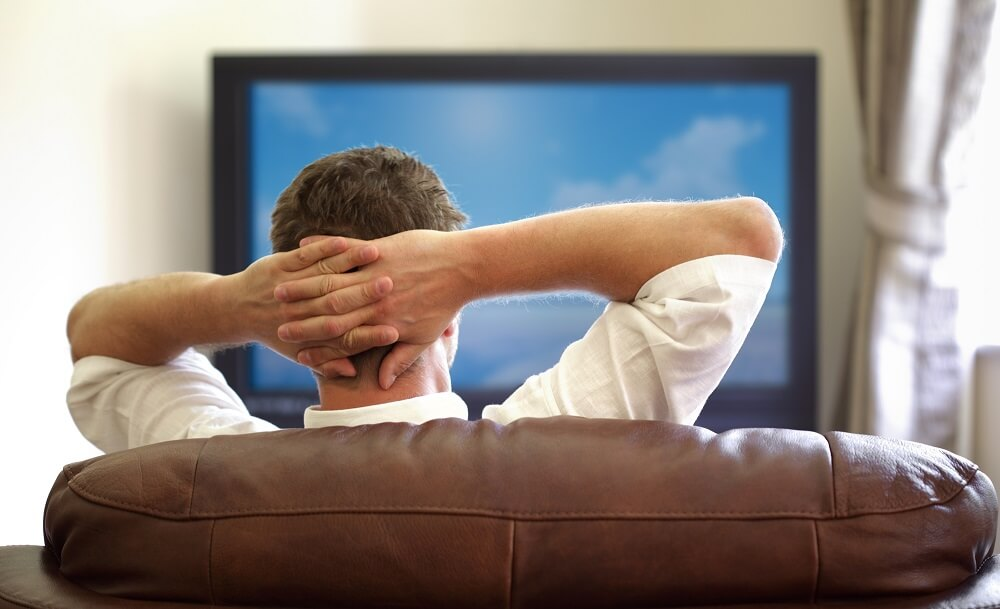 man relaxing while watching tv