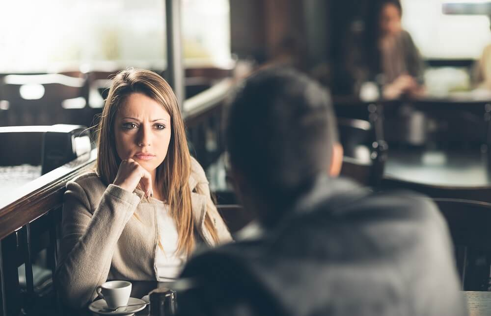 woman looking at man across the dinner table