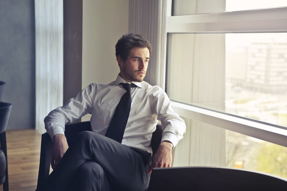 business man stressed looking out window