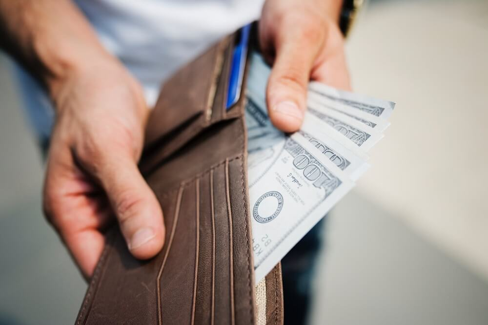 man showing wallet full of money