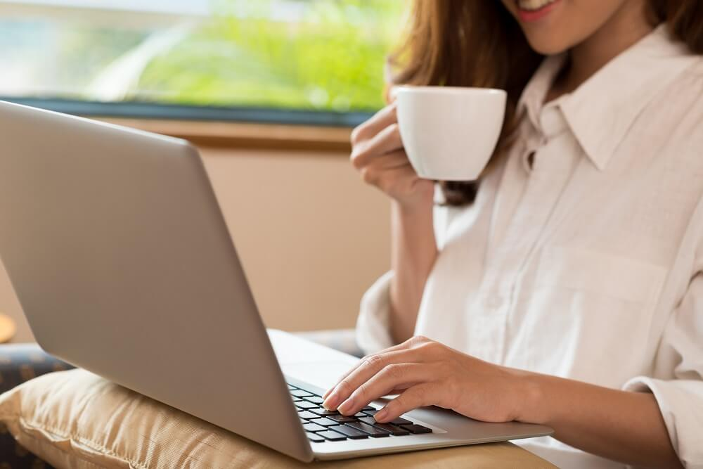 woman drinking coffee while using her laptop