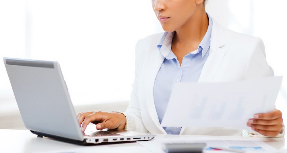 woman doing paperwork on computer