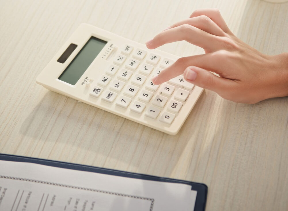 woman calculating bills as one of her debt reduction strategies