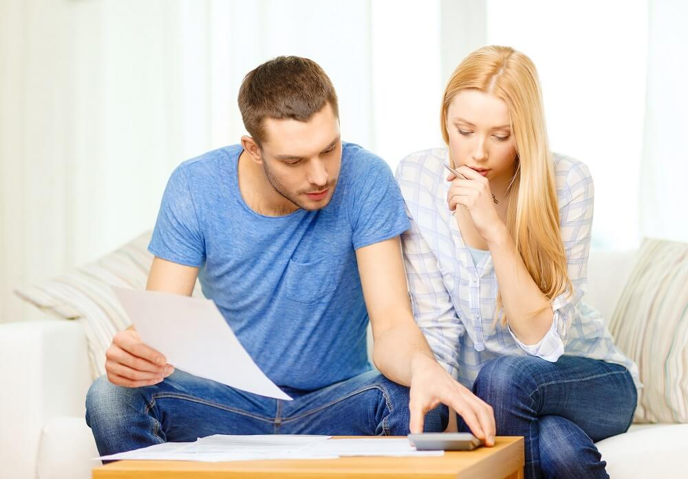 couple looking at bills in dave ramsey budget percentages article