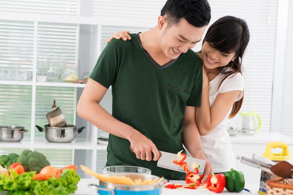 woman and man cooking at home using smart money making moves
