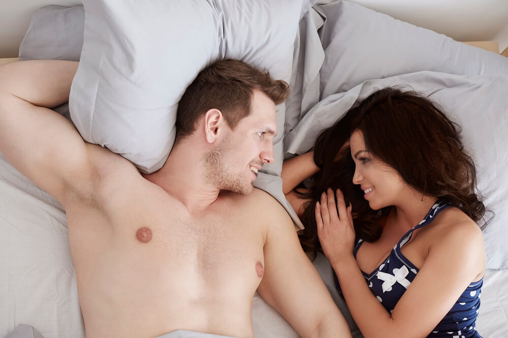 couple cuddling in bed - sex tips for men