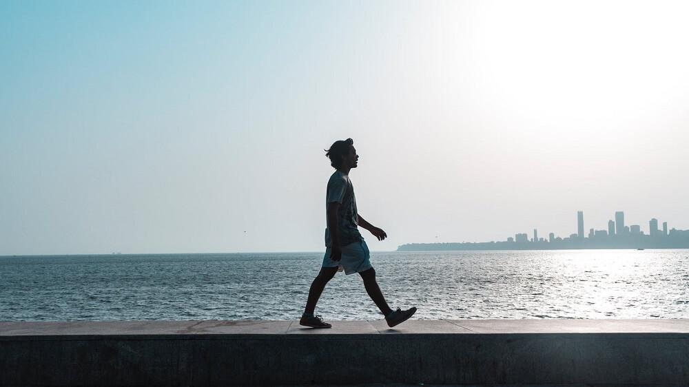 man walking by beach