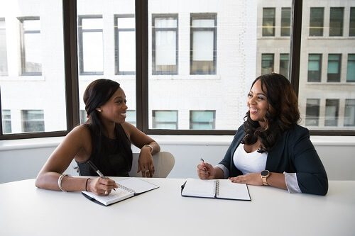 two women talking at business table
