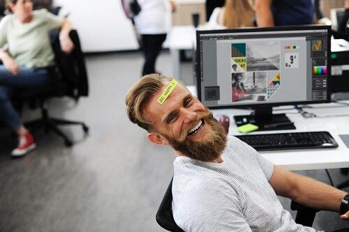 man smiling at work desk